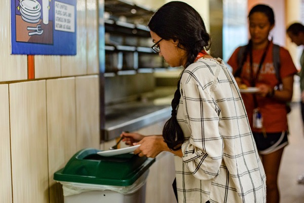 UT Dallas student scraping food into bin.